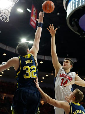 Arizona center Dusan Ristic shoots over Michigan forward Ricky Doyle (32) during the second half of an NCAA college basketball game, Saturday in Tucson, Ariz.
