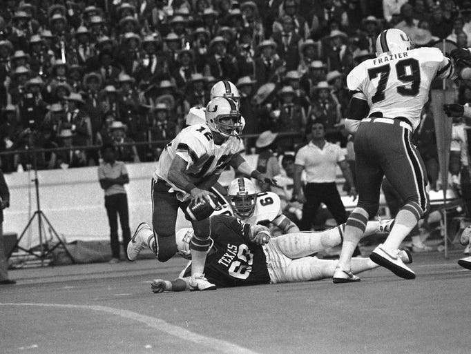 Miami quarterback Jim Kelly moves around Texas linebacker Tony Edwards to pick up four yards on a keeper play Sept. 26, 1981.