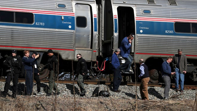 Passengers watch as emergency personnel work at the scene of a train crash involving a garbage truck in Crozet, Va., Jan. 31, 2018. The Amtrak passenger train carrying dozens of GOP lawmakers to a Republican retreat in West Virginia struck a garbage truck south of Charlottesville, Va.