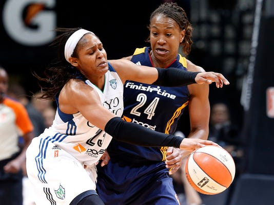Minnesota Lynx forward Maya Moore (23) drives on Indiana Fever forward Tamika Catchings (24) in the second half of Game 5 of the WNBA basketball finals, Wednesday, Oct. 14, 2015, in Minneapolis. (AP Photo/Jim Mone)