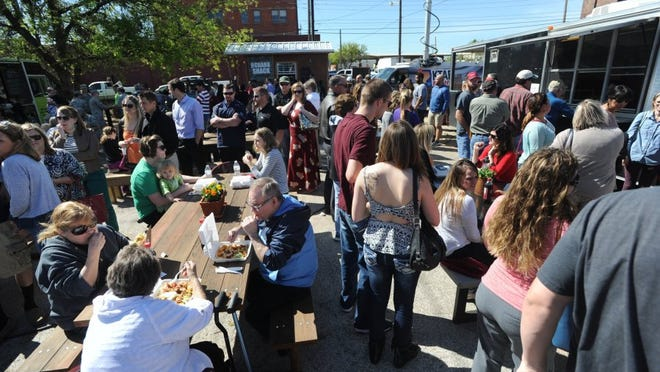 PHOTOS BY Nellie Doneva/Reporter-News Lines for food snake around the picnic tables at the food truck event on South 1st Street Tuesday. Food and live music entertained the crowd.