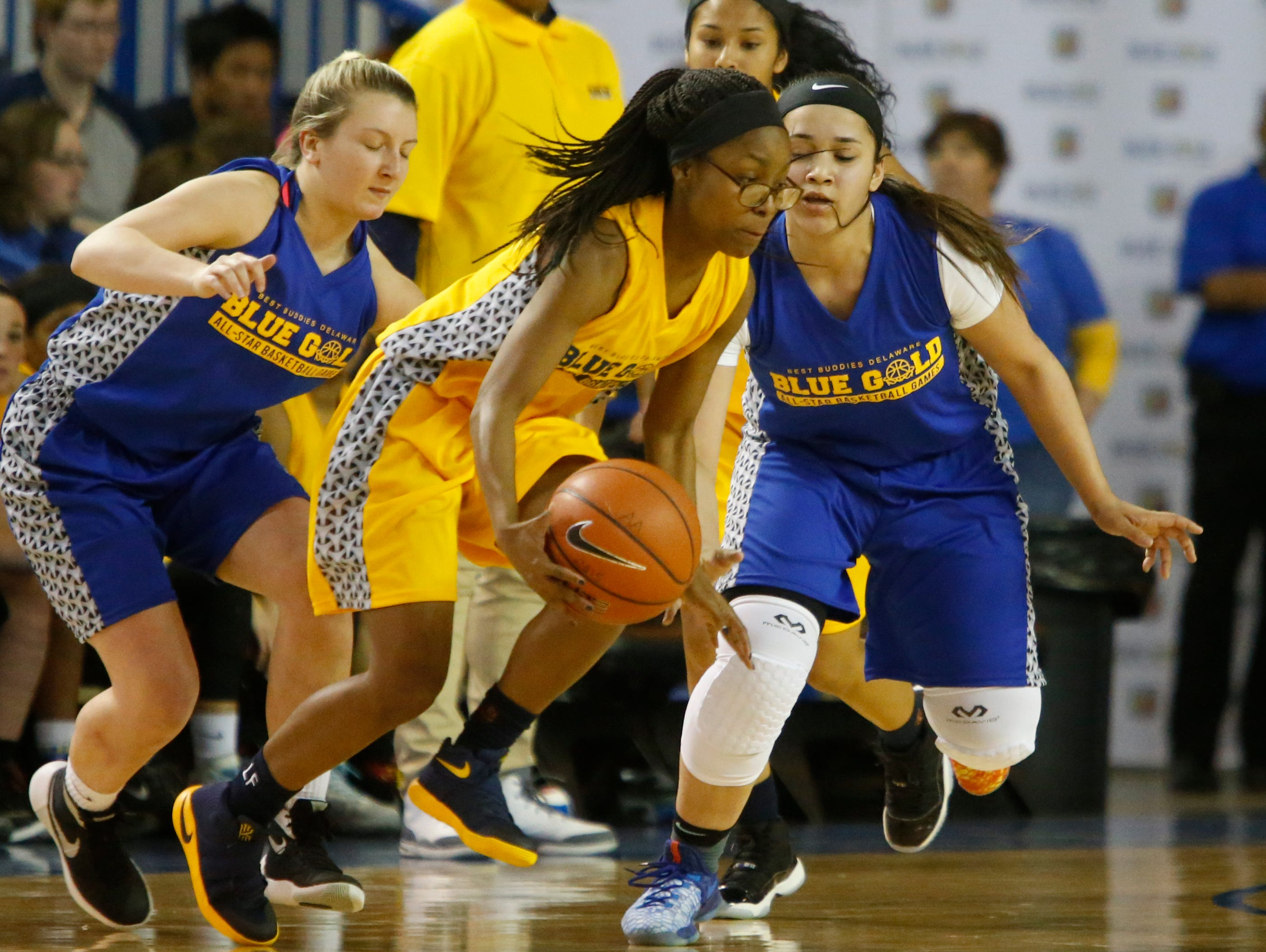 Gold's Arika Burrell of Lake Forest (center) is defended by Blue's Lexi Bromwell of St. Elizabeth (left) and Jaylin Ortiz of Delcastle in the second half of the Blue-Gold All-Star Basketball game at the Bob Carpenter Center Saturday. Blue won, 66-54.