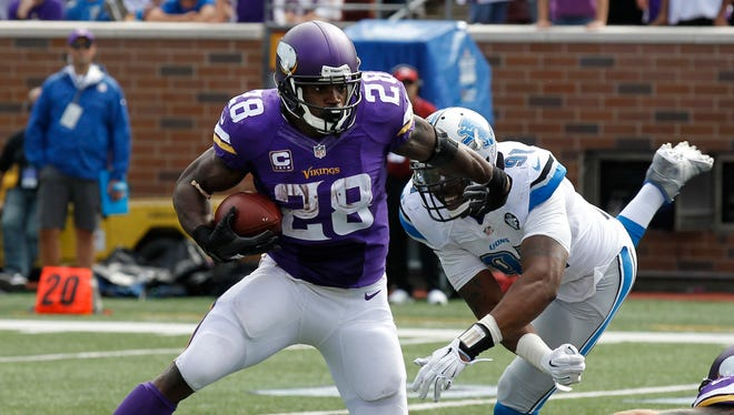 Vikings running back Adrian Peterson runs in the second half of the Lions' loss Sunday in Minneapolis.