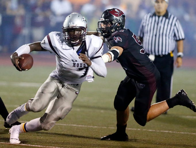 Hodgson's Ray Jones tries to elude Caravel's Johnny Zitofsky in the second quarter of the Bucs' 39-8 win in the DFRC Kickoff Classic at Caravel's Bob Peoples Stadium, Sept. 4, 2014.