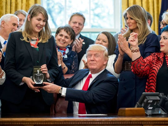 President Donald Trump, accompanied by Vice President Mike Pence, left, and first lady Melania Trump, center right, as he presents the 2017 National Teacher of the Year award to Codman Academy 9th grade humanities teacher Sydney Chaffee of Dorchester, Mass, second from left, during a ceremony in the Oval Office at the White House in Washington, Wednesday, April 26, 2017.