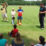 The Matrix Soccer Academy's Charlie Jackson walks through a drill with campers Thursday.