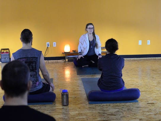 Yoga teacher Brandy Oswald speaks to participants in