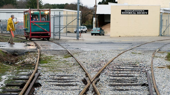 A flagman guides a train car across a road in Stewartstown near the station.  Paul Kuehnel - Daily Record/Sunday News