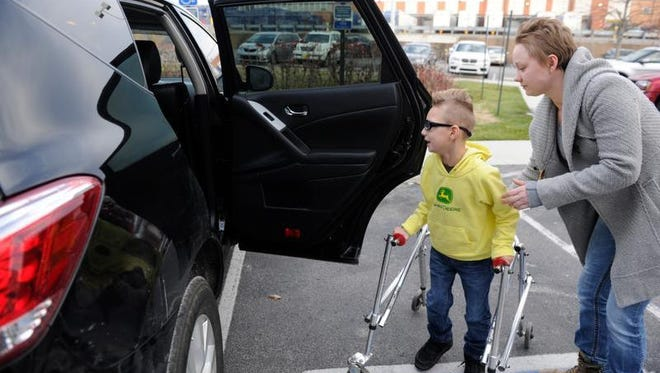 Nina Vaden helps her son Skylar, who has cerebral palsy, in and out of their family vehicle outside the 100 Oaks Vanderbilt clinic. Vaden depends on a grant program to help pay for her to drive from Stewart County to Vanderbilt every week for Skyler to get physical therapy and speech therapy.