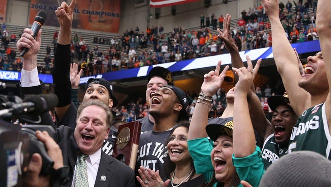 Michigan State head coach Tom Izzo celebrates with his team after the 76-70 overtime win against the Louisville Cardinals in the NCAA East Regional Final on Sunday, March 29,2015 at Carrier Dome in Syracuse N.Y.