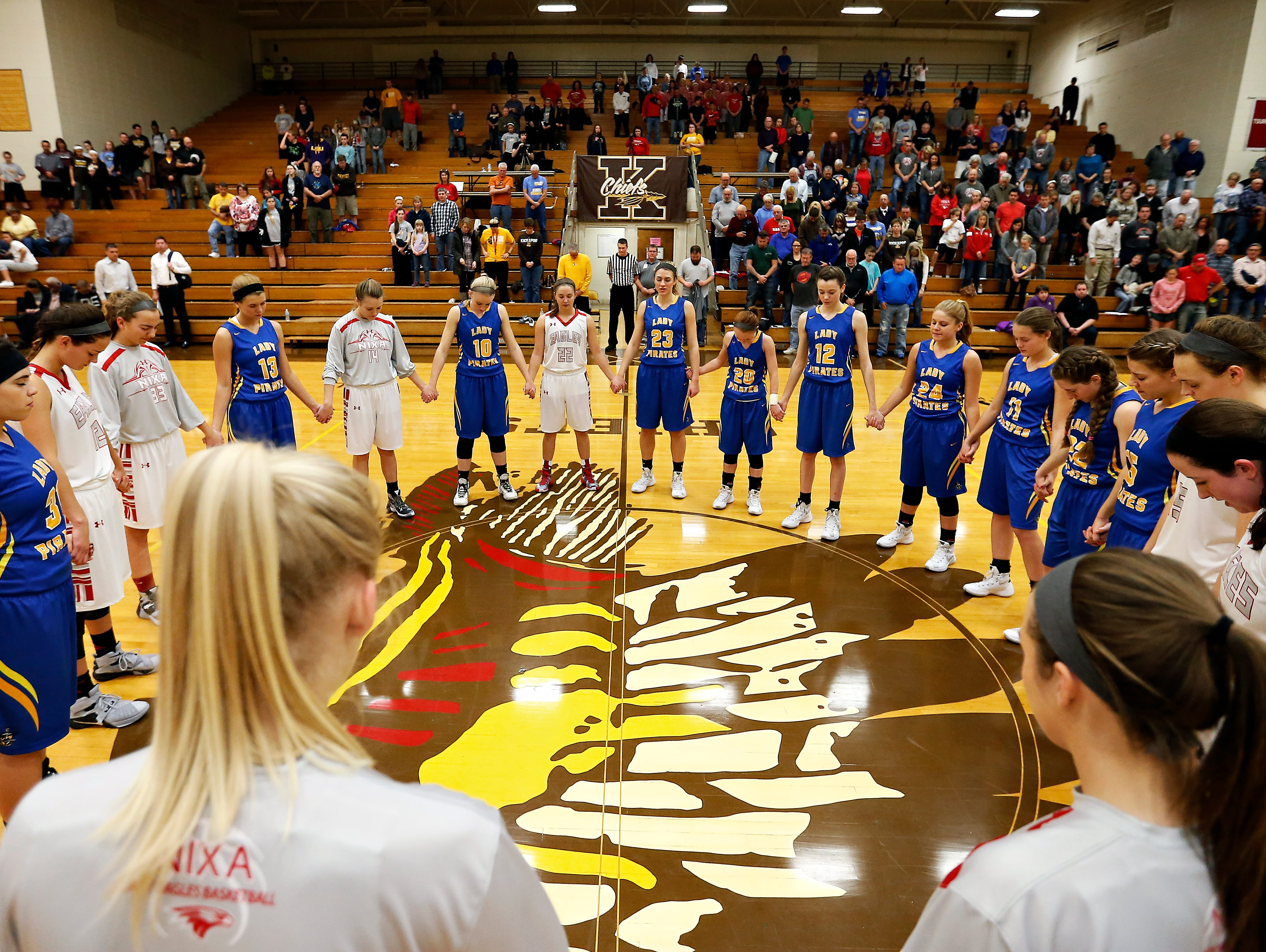 Crane High School forward Emma Lander (23) leads the Lady Pirates and the Nixa Eagles in prayer before the start of their game at Kickapoo High School in Springfield, Mo. on Dec. 11, 2015.