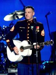 Marine Staff Sgt. Brandon Valentine performs onstage