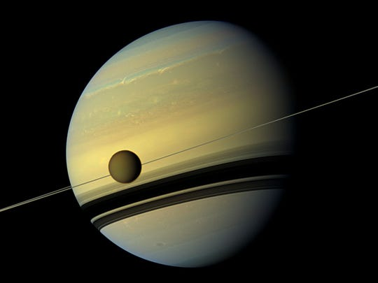 The moon, Titan, in front of Saturn and its beautiful rings.