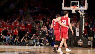 Ethan Happ (left) and Zak Showalter of the Wisconsin Badgers walk off the court after being defeated by the Florida Gators in overtime, 84-83, in the 2017 NCAA Tournament East Regional at Madison Square Garden.