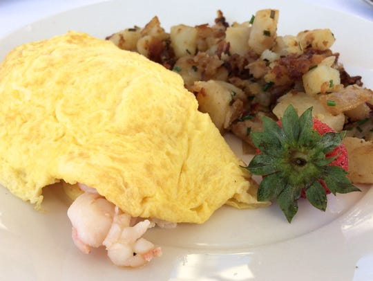 A shrimp and lobster omelet with fresh home fries is