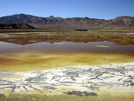 In this Nov. 30, 2004, file photo, an evaporation pond holds contaminated fluid and sediment at the former Anaconda copper mine near Yerington.