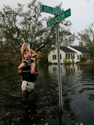 Maria MagInnis is carried from their home by her husband David Maginnis in the high flood waters after the residents of the Old Metairie section of the City of Metairie in Jefferson Parish were allowed to return to home one week after being evacuated from Hurricane Katrina.