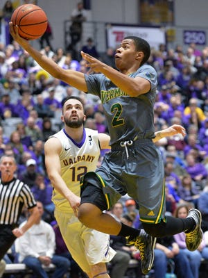 Vermont's Trae Bell-Haynes drives to the hoop past Albany's Peter Hooley, left, during Saturday's America East Conference men's basketball game. Albany won 75-71.