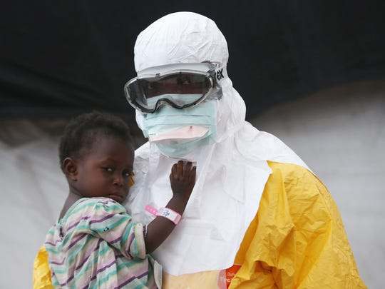 A Doctors Without Borders health worker in protective clothing made by DuPont holds a child suspected of having Ebola in a treatment center on Oct. 5 in Paynesville, Liberia. The girl and her mother were awaiting test results for the virus.