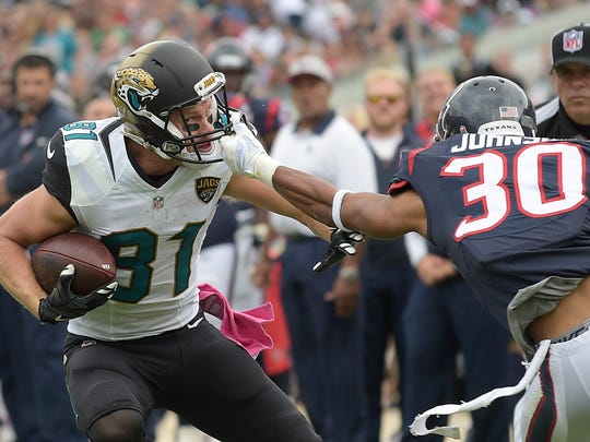 Houston Texans free safety Kevin Johnson (30) grabs the face mask of Jacksonville Jaguars wide receiver Bryan Walters (81) as he tries to make a tackle during the first half of an NFL football game in Jacksonville, Fla., Sunday, Oct. 18, 2015.(AP Photo/Phelan M. Ebenhack)