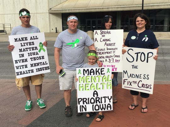 Participants at the March to the Capitol for Mental Health hold signs while waiting to march in the Cowles Commons.