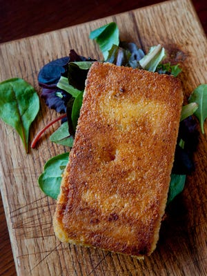 The smoked cheddar grit cake at Hammerheads is made from smoked cheddar cheese, grits, chicken broth, crushed red pepper, adobo seasoning, bay leaves and butter and is pan fried until golden brown then served atop a spring mix of salad.Jan. 04, 2018