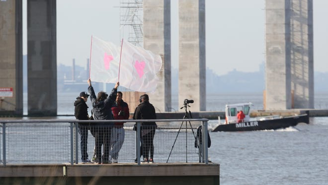 Family members wave flags with a pink heart, as the tugboat Specialist is raised to the surface of the Hudson River under the Tappan Zee bridge, March 24, 2016, as emergency workers recover the body of Harry Hernandez and perform forensic examination on the vessel.