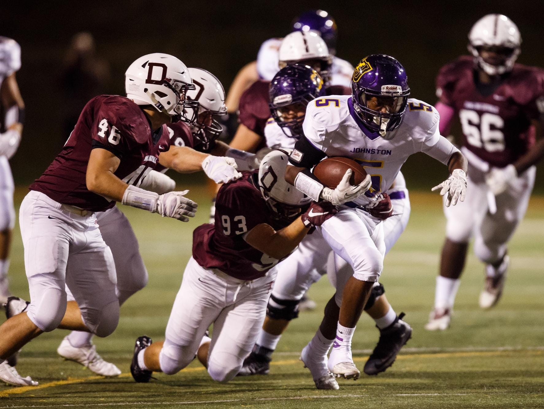 Johnston's T-Boy White is tackled by Dowling Catholic's Nico Scigliano during Friday's game at Valley Stadium. The unbeaten Maroons (6-0) punished Johnston 35-15 to clear their last significant hurdle to an unbeaten regular season.