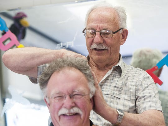 """Don """"Andy the Barber"""" Andersen gives Pastor Jack Bell a trim while cracking jokes about Donald Trump's hairstyle at his Stanford barbershop. On May 5, Andersen will celebrate 55 years as a barber in Stanford and 58 total years of experience in his trade. He aims for at least 60 years in the profession."""