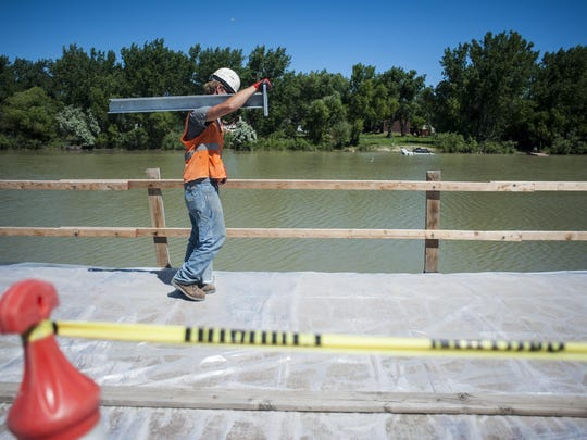 Kellee States places steel handrails to match the walking path across the 10th Avenue South bridge Wednesday.