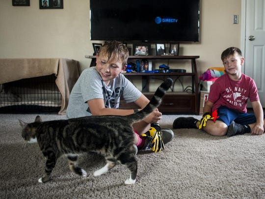 Steven Triplett and Jaden Mann, a family friend, sit in the living room with the family cat, Summer. When the family was chosen for the home, Habitat for Humanity told Steven first, but his grin was too big to keep the surprise from his parents.