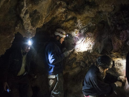Left to right, Dave Bottitt, Steven Jenkins, and Johanna Kovarik scrub graffiti off of walls in Lick Creek Cave using wire brushes and water hauled through the cave in 50 pound bags Friday.