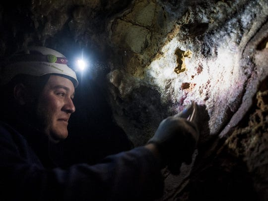 Steven Jenkins, a caver with the Northern Rocky Mountain Grotto, scrubs at graffiti on the walls of Lick Creek Cave with a wire brush.