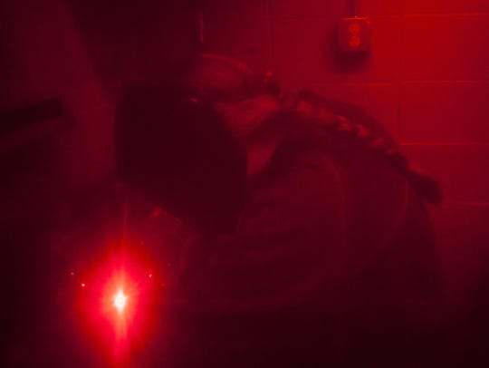 Photographed from behind a protective red curtain,