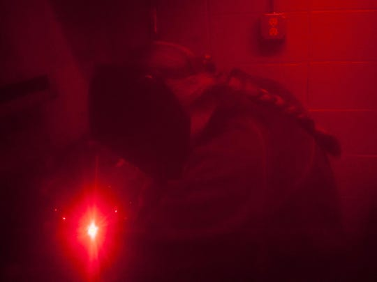 Photographed from behind a protective red curtain, Tiffanie Carter practices an arc weld at C.M. Russell High on Monday.