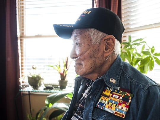 Andrew Kim, who was a 15-year-old boy living in Pearl Harbor during the attack, sits at his kitchen table wearing his veteran cap and ribbons from his military career.