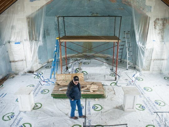 Mike Habets walks through the Sacred Heart Church east of Valier on April 12. Soon the church's belfry and original bell will be replaced along with other repairs such as adding roof insulation, wiring and repainting the original plaster walls.