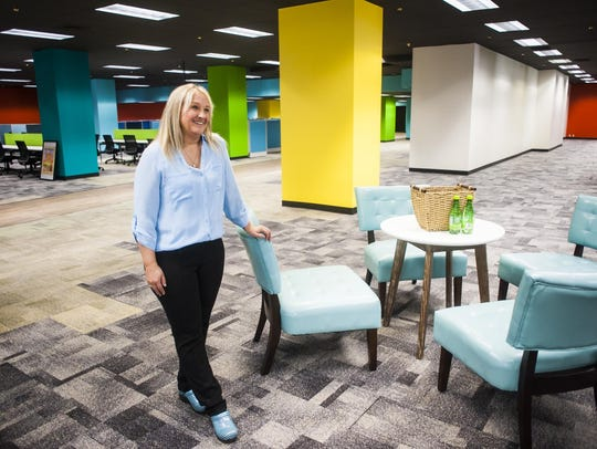 FCR human resources manager Holli Lanes leans on a chair during a tour of the colorful new call center at 410 Central Ave.