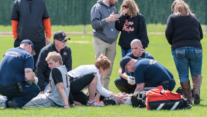 Marshfield High School baseball players Trevor Schwecke, 17, left, and Braden Bohman, right, receive treatment after they collided Saturday during a baseball game against Chippewa Falls at Jack Hackman Field in Marshfield.
