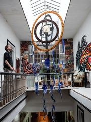 Windwalker Underground Gallery artist and board member Vincent Brady shows the Craig Mitchell Smith glass dream catcher hanging from the skylight at the gallery Monday, Oct. 23, 2017.