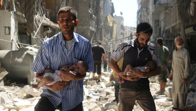 Syrian men carrying babies make their way through the rubble of destroyed buildings following an air strike on the rebel-held Salihin neighbourhood of the northern city of Aleppo, on Sept. 11, 2016.