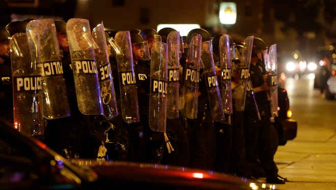 Police move in on a crowd throwing rocks at police in Milwaukee during a protest Sunday following a police shooting that killed Sylville Smith on Saturday.