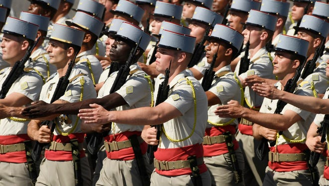 Military personnel march in a traditional military parade as part of the Bastille Day celebrations in Paris.