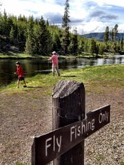 Visitors fish in Yellowstone National Park on the Firehole River.