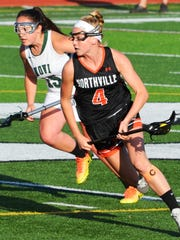 Northville's Sarah Chase (right) carries the ball with Novi's Rachel Bayer in hot pursuit.