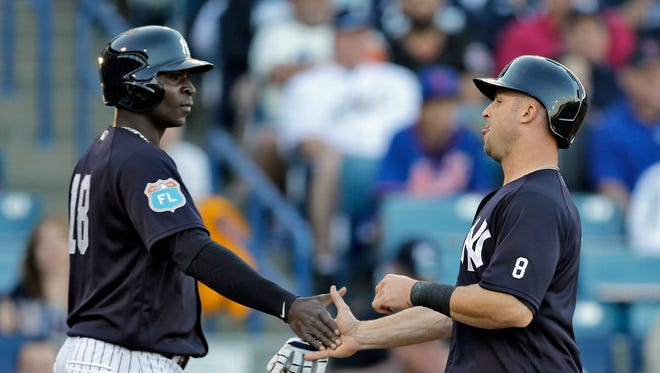 New York Yankees' Brett Gardner, right, and Didi Gregorius celebrate after scoring on a two-run single by Alex Rodriguez off New York Mets starting pitcher Steven Matz during the second inning of a spring training baseball game Tuesday, March 22, 2016, in Tampa, Fla.