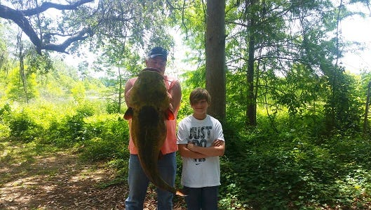 Charles Patchen, 13, caught this 63.8 pound flathead catfish, held by his stepfather  Bryan Atwell, in Jackson County, Fl., breaking a previous state record.