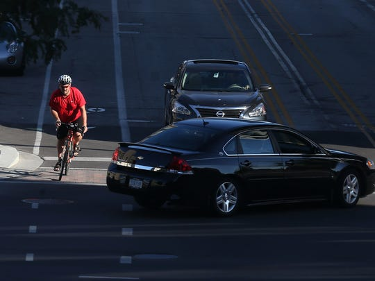 A cyclist navigates downtown Cedar Rapids in the designated bicycle lanes.