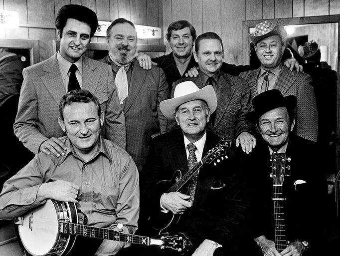 Gathered around the Father of Bluegrass Music at the Early Bird Bluegrass Concert on Oct. 13, 1971, are the participants who once were members of Bill Monroe's Bluegrass Boys. Standing are Monroe's son James, left, leader of the Midnight Ramblers; Mac Wiseman; Bill Yates of the Country Gentlemen; Ralph Stanley, leader of the Clinch Mountain Boys; and Jimmy Martin, leader of the Sunny Mountain Boys. Seated are Don Reno, of Reno, Smiley, Harrell and the Tennessee Cut-Ups; Bill Monroe; and Lester Flatt, leader of the Nashville Grass.