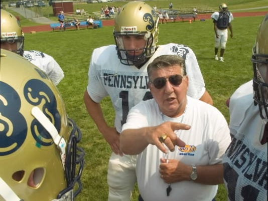George Chaump, head coach of the Pennsylvania Big 33 football team, gives instructions to the squad during a practice. Former Penn State player Anthony Morelli, rear, listens in.